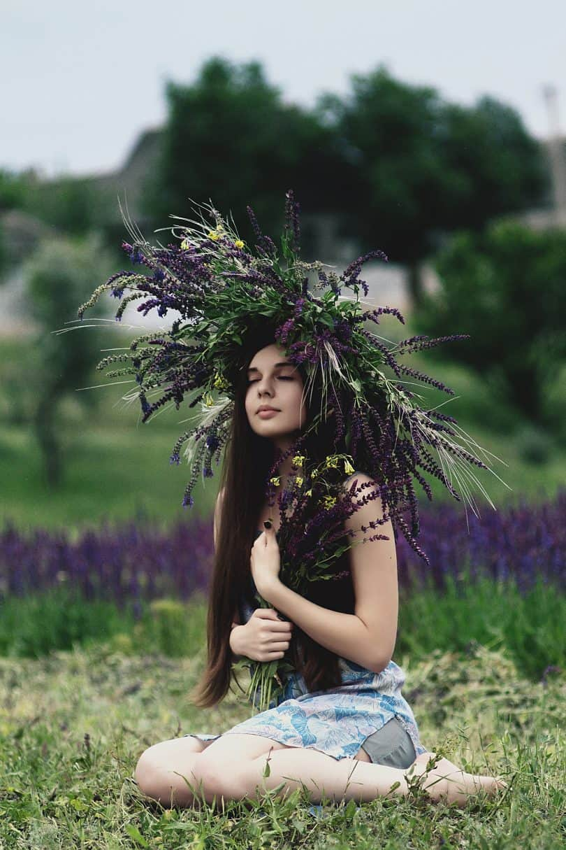 Beautiful girl in lavender farm holding lavender wreath